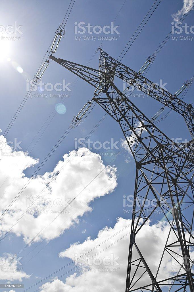 Power electricity pylon against the sun on blue sky royalty-free stock photo