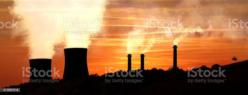 Power generating factories in the mountains at sunset backlight stock photo