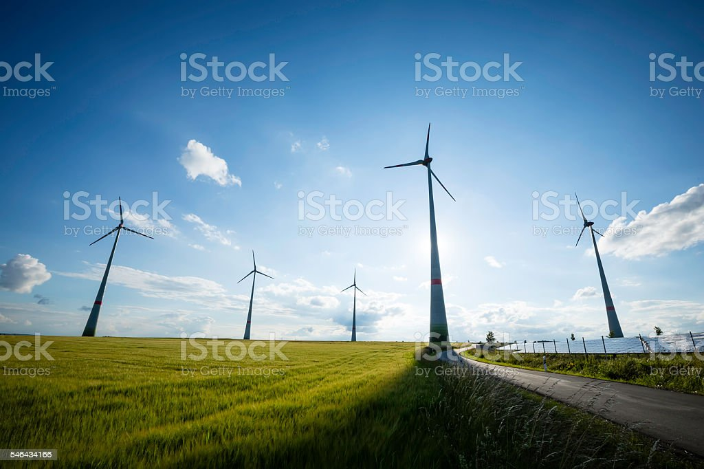power generating wind turbines and modern solar panels at sunset stock photo