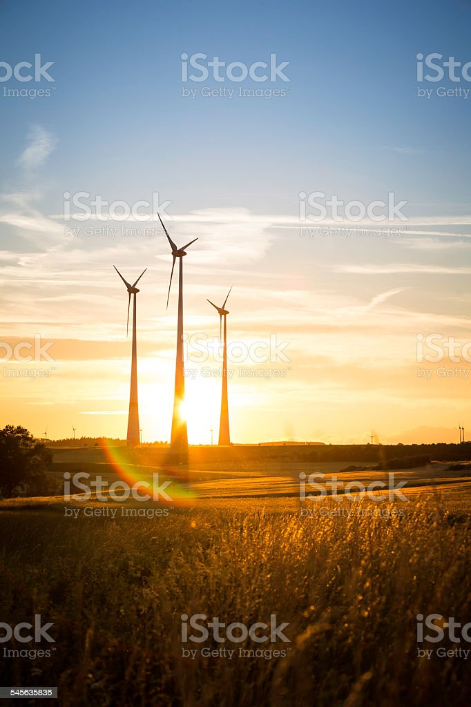 power generating wind turbines in the countryside in the evening stock photo