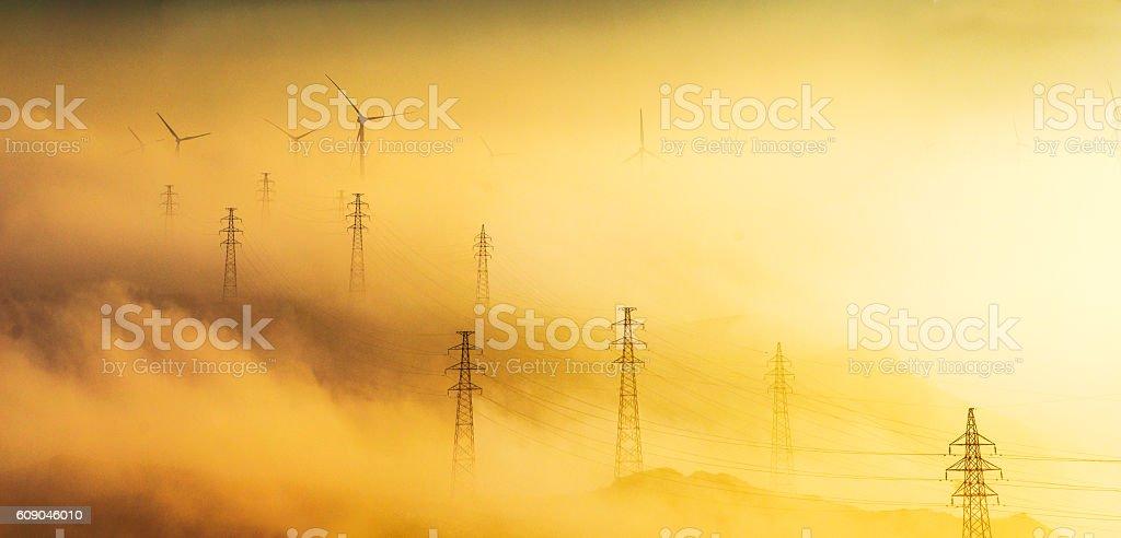 Power Generating Windmills and Electricity pylon stock photo