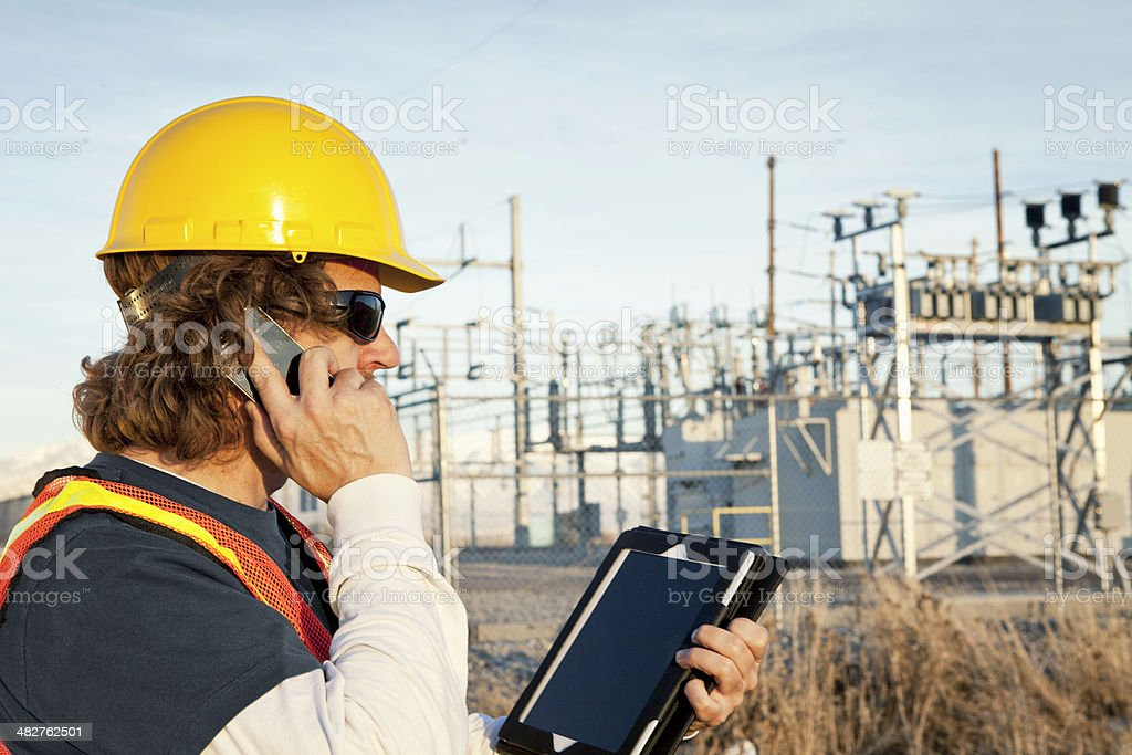Power Line Technician Using Phone and Tablet stock photo