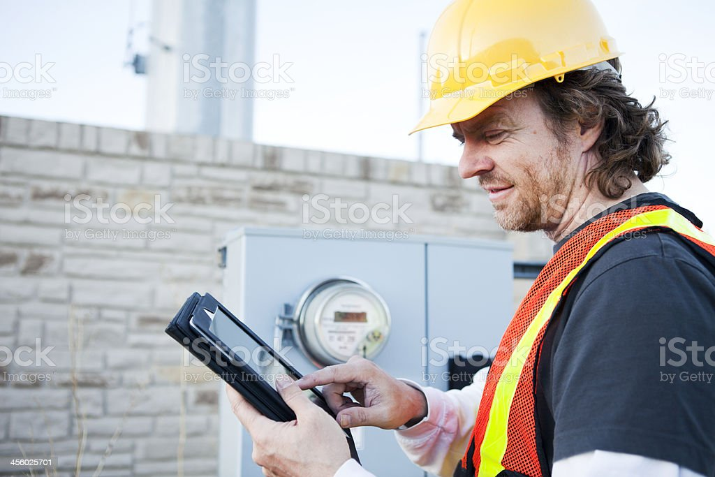 Power Line Technician Using Tablet Computer stock photo