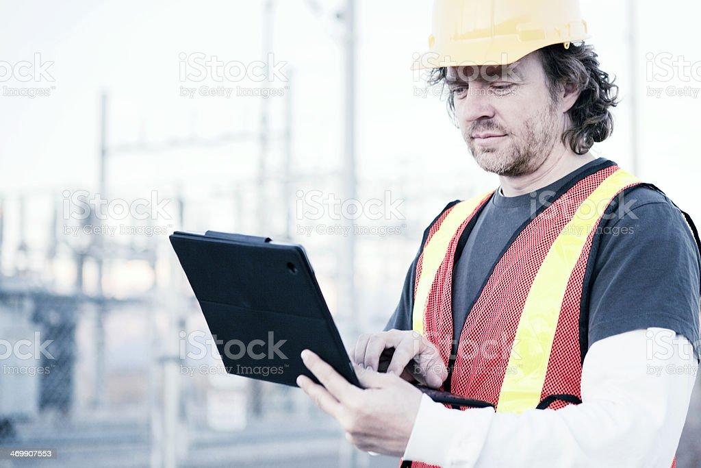 Power Line Technician Using Tablet Computer stock photo