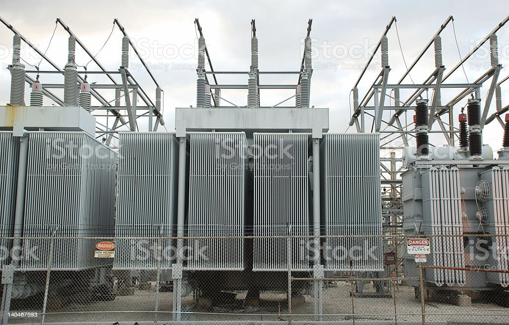 Power lines and generators with high voltage signs royalty-free stock photo