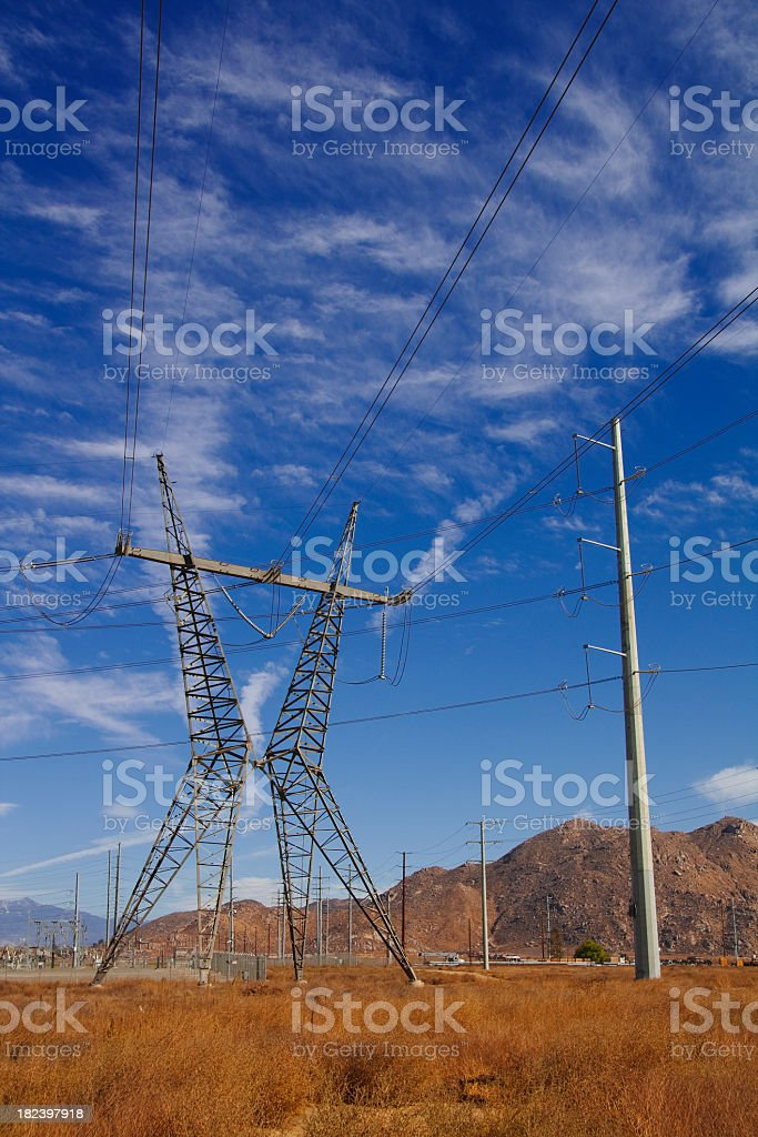 Power lines and pylon against a blue sky stock photo