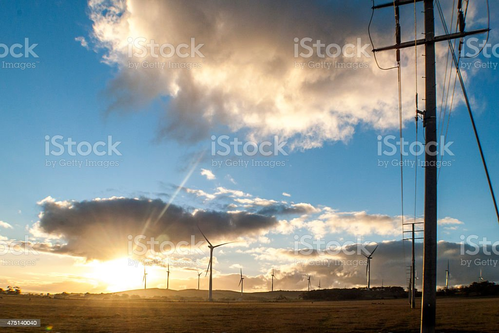 power lines and wind turbines in a field stock photo