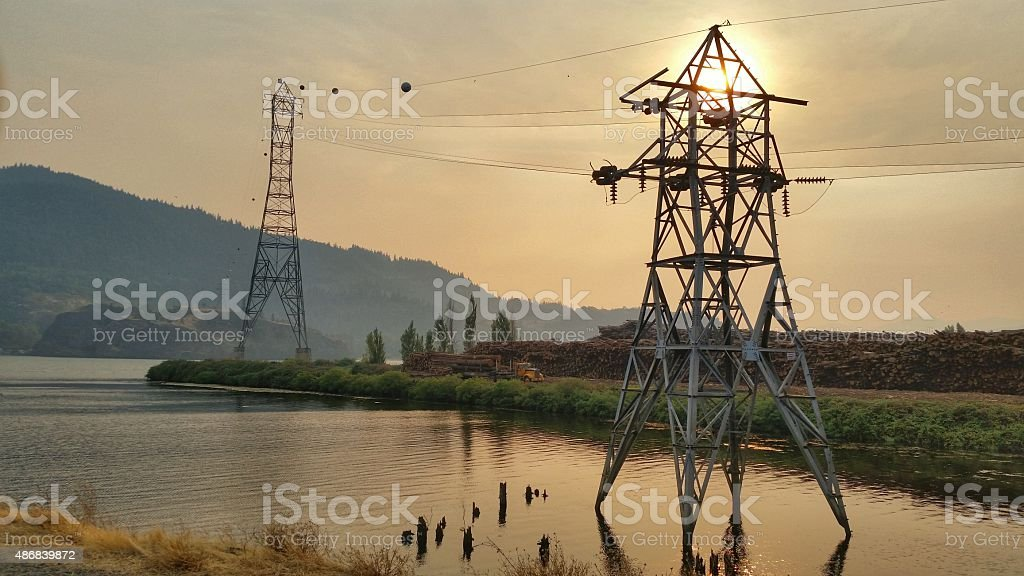 Power lines are silhouetted by the sun stock photo