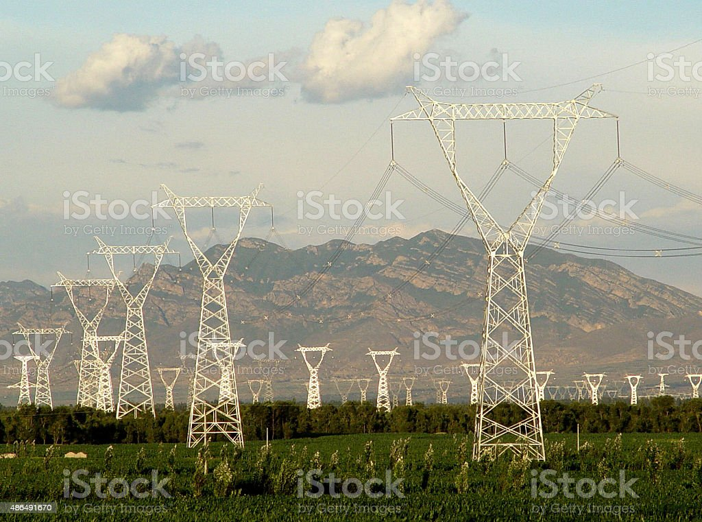 power lines in green field-high voltage pylons stock photo