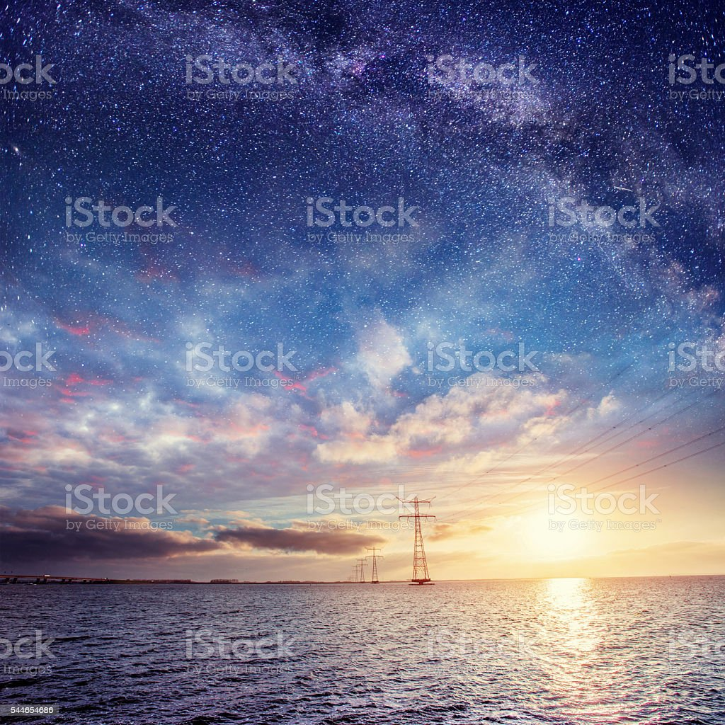 Power lines over water at night. Mysterious starry sky. stock photo