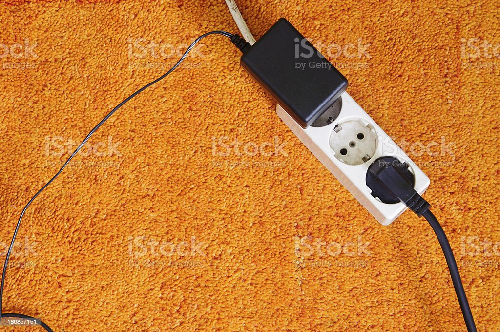 Power outlet on orange carpet from above stock photo