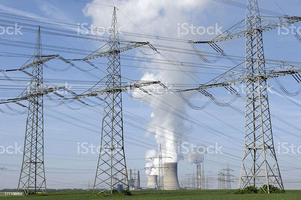 Power plant between three electricity pylons stock photo