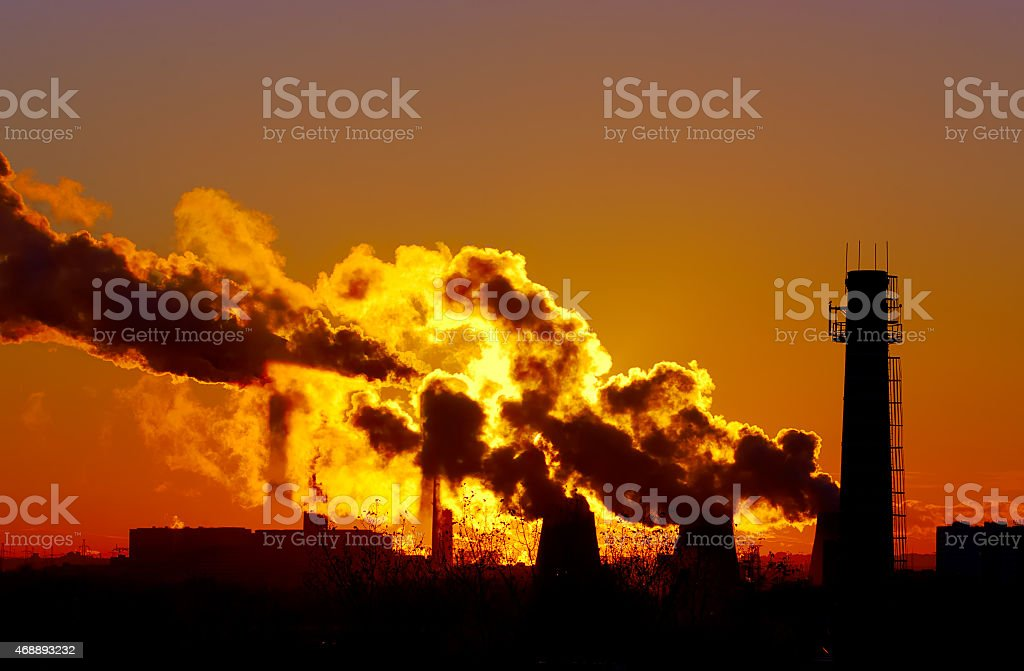 power plant smokestacks at sunset stock photo