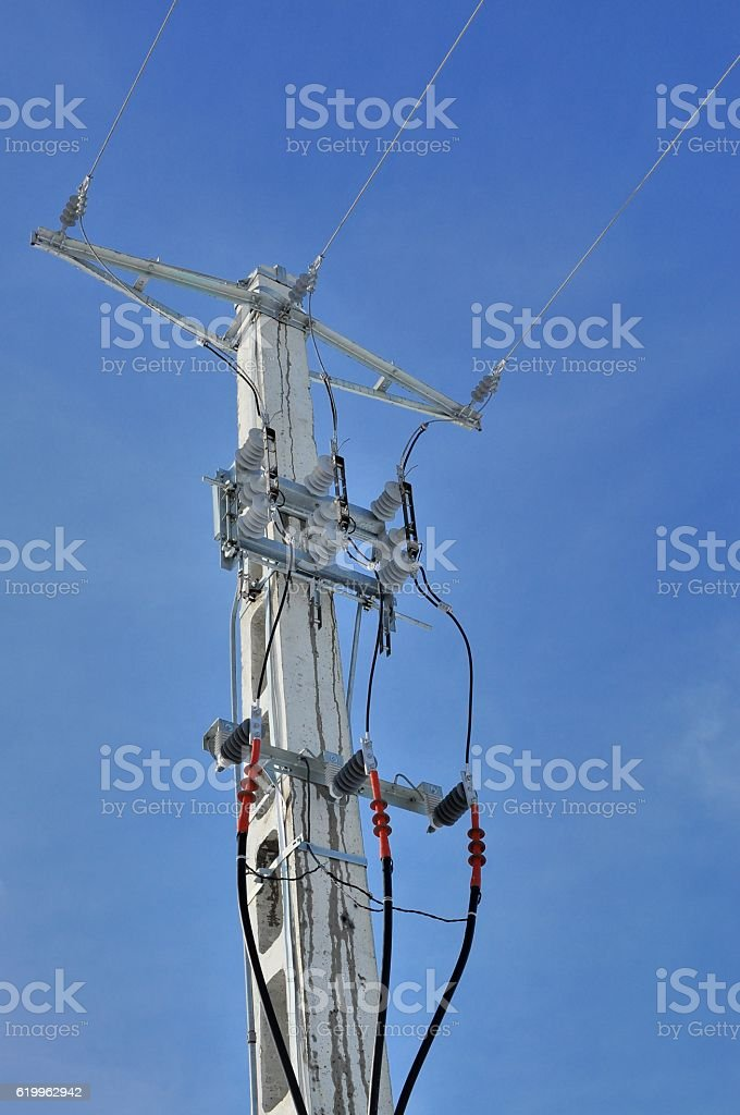 Power pole with external electric separator against the blue sky stock photo