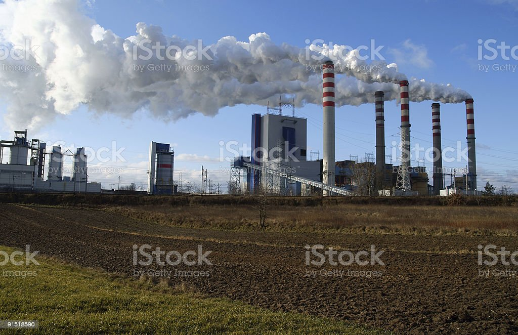 Power station in in countryside with chimney releasing smoke royalty-free stock photo