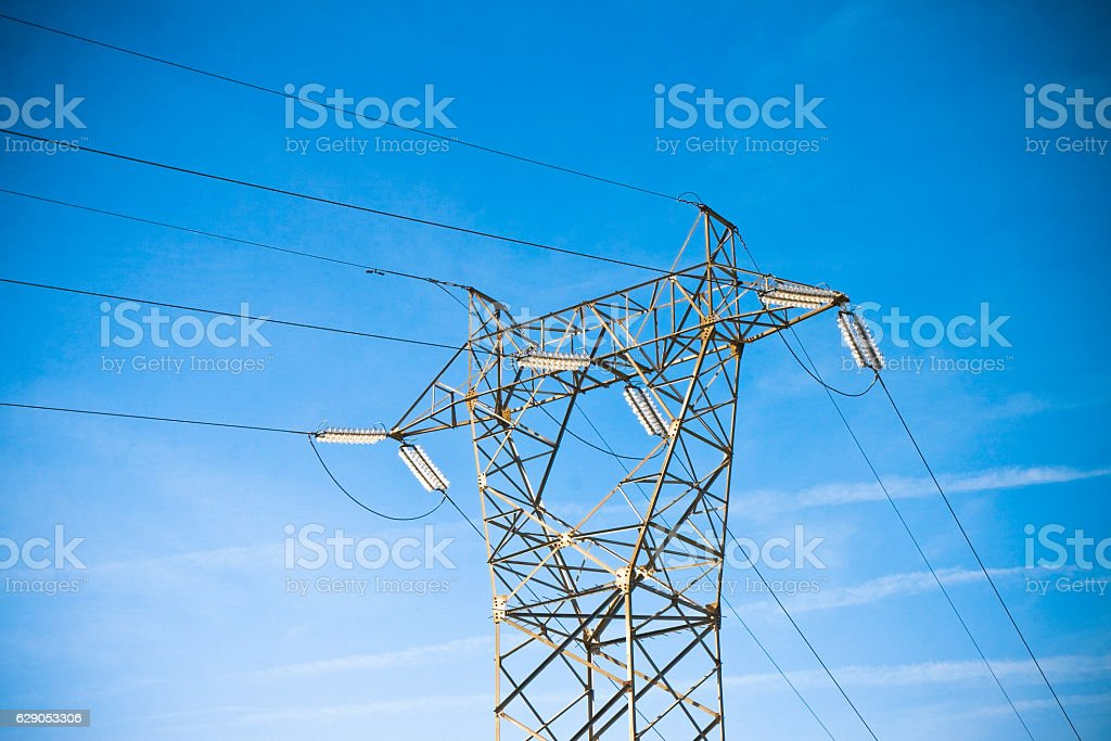 Power tower and transmission lines on blue background stock photo
