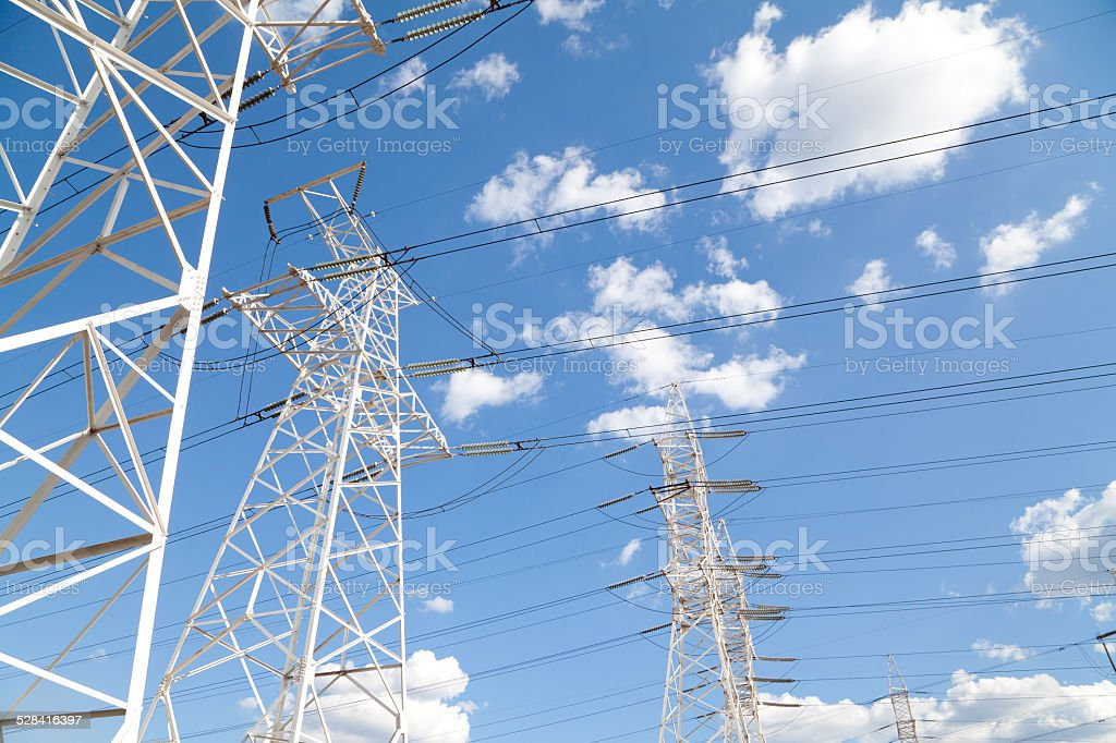 Power transmission lines against blue sky stock photo