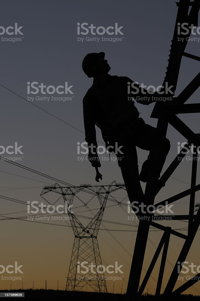 Power utility worker silhouetted stock photo