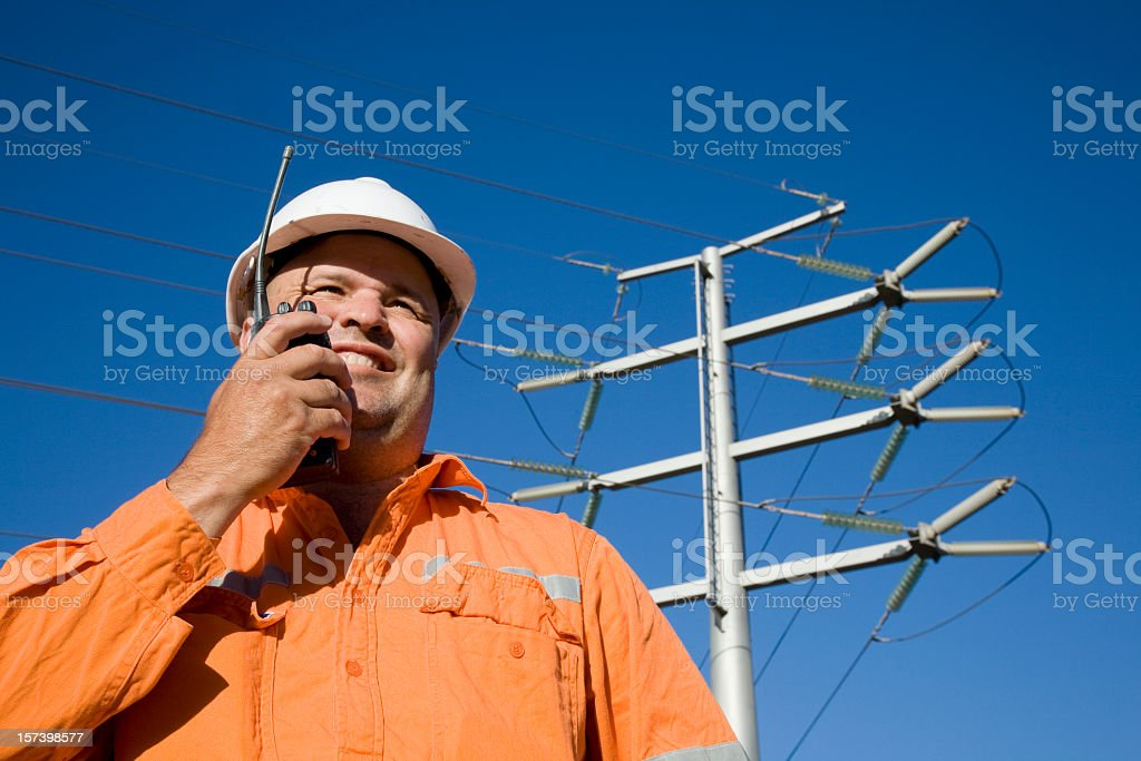 Power worker relaying info over walkie talkie royalty-free stock photo