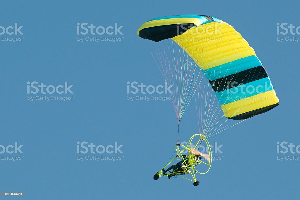 powered parachute flying in clear blue sky royalty-free stock photo