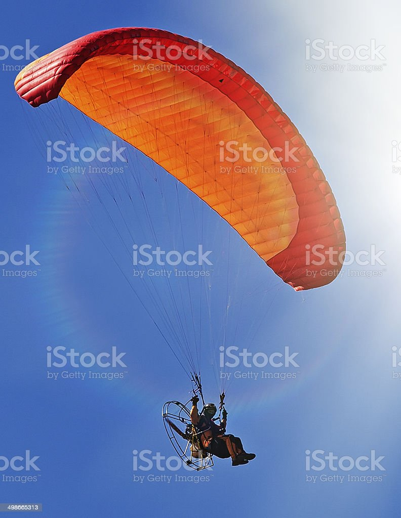 Powered paraglider flying into the sky stock photo