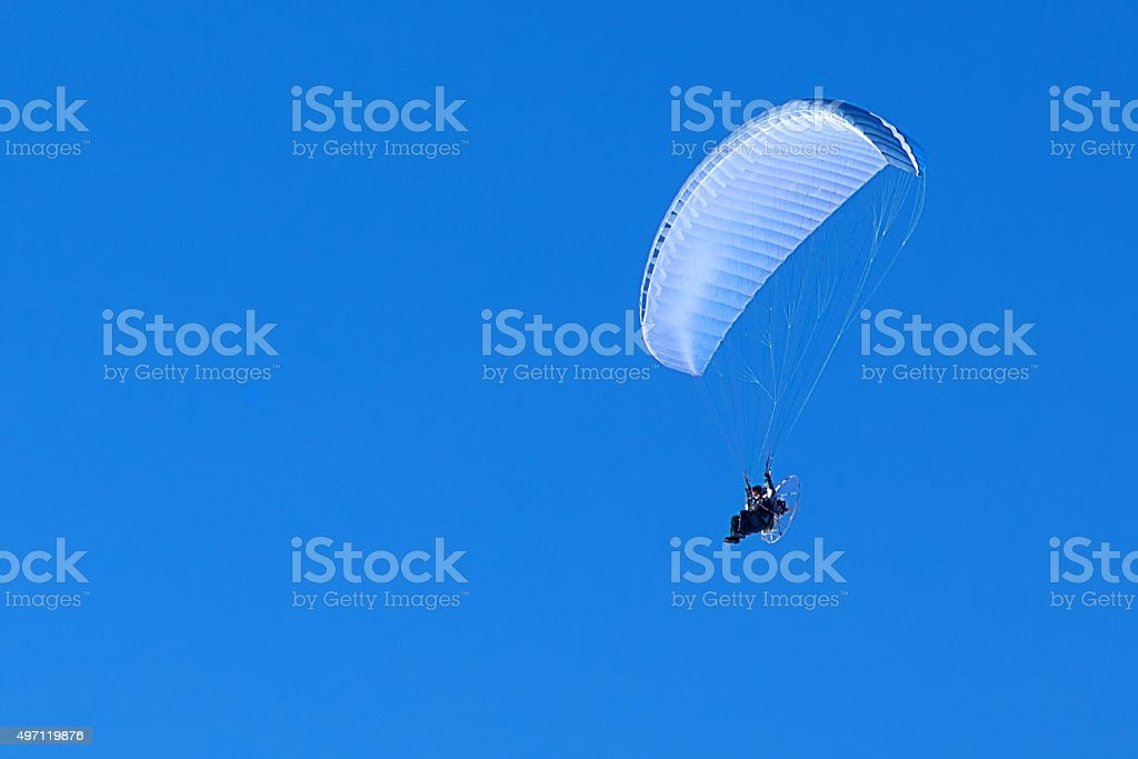 powered paragliding in the blue sky stock photo