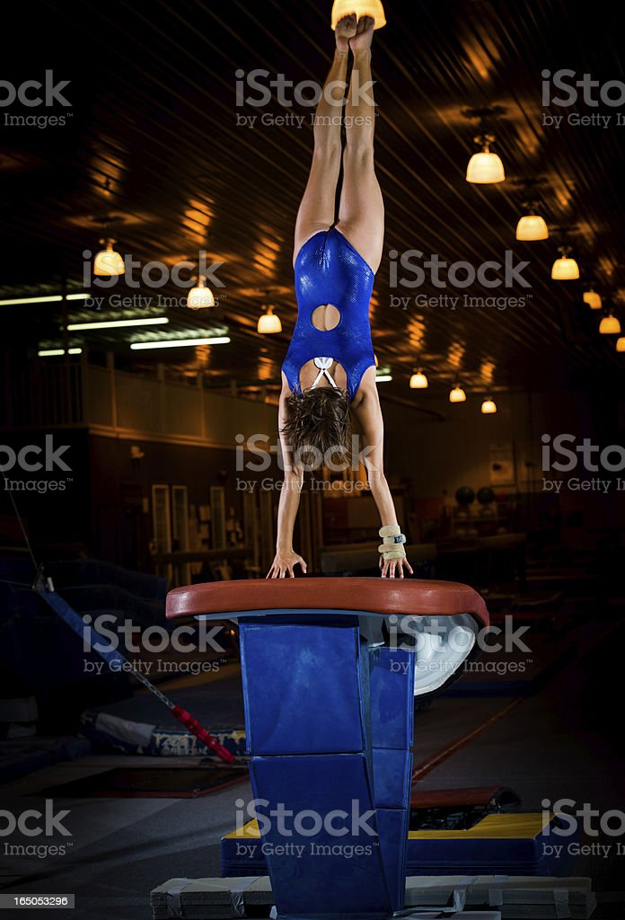 Powerful Female Gymnast in Springing off Vault stock photo