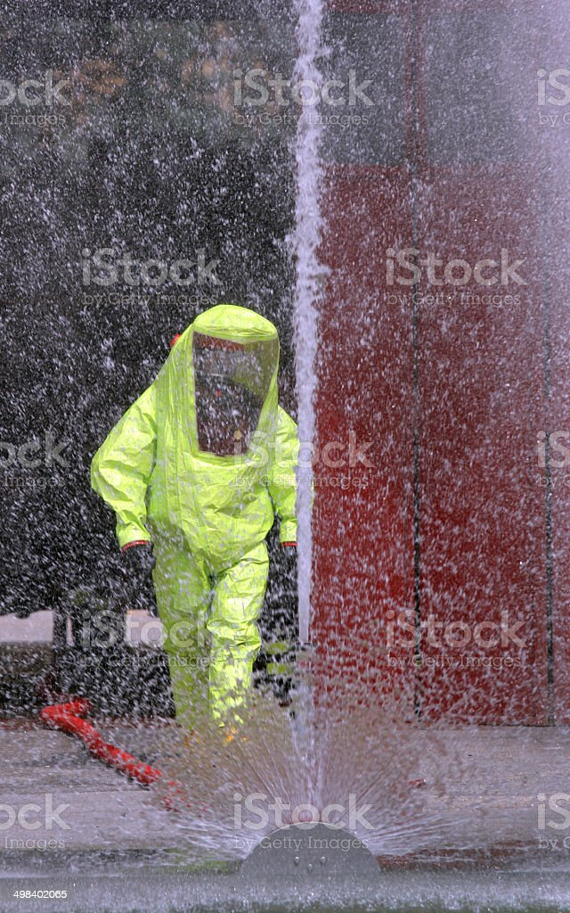 powerful jet of water to wash the yellow suit stock photo