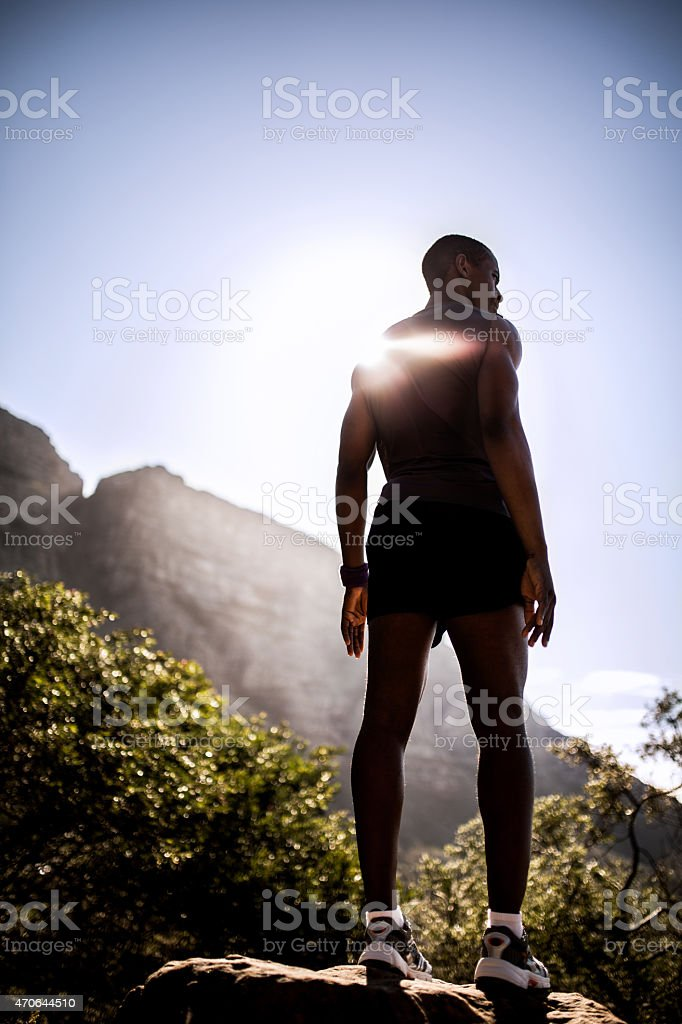 Powerful male athlete standing atop a mountain stock photo