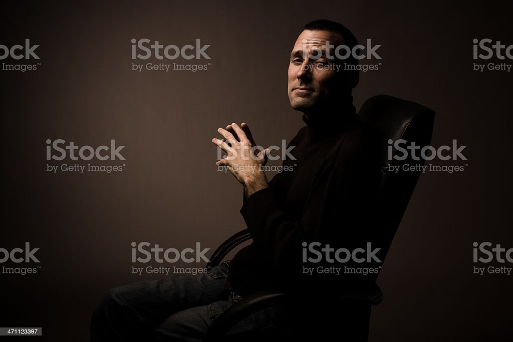 Powerful man sitting in chair squinting at camera royalty-free stock photo