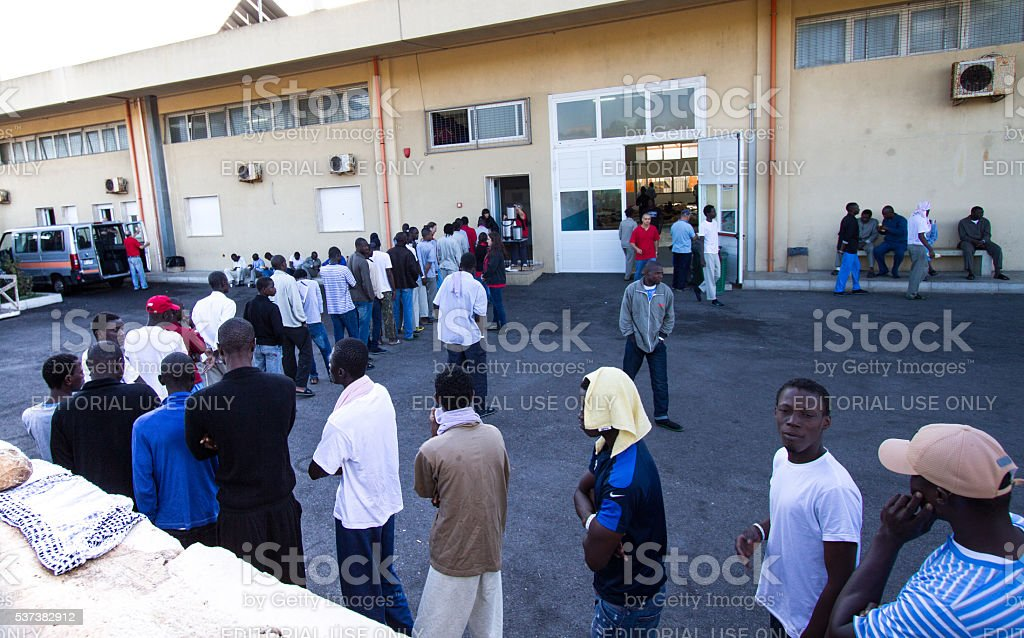 Pozzallo, Sicily: African Migrants Wait for Breakfast at Reception Center stock photo