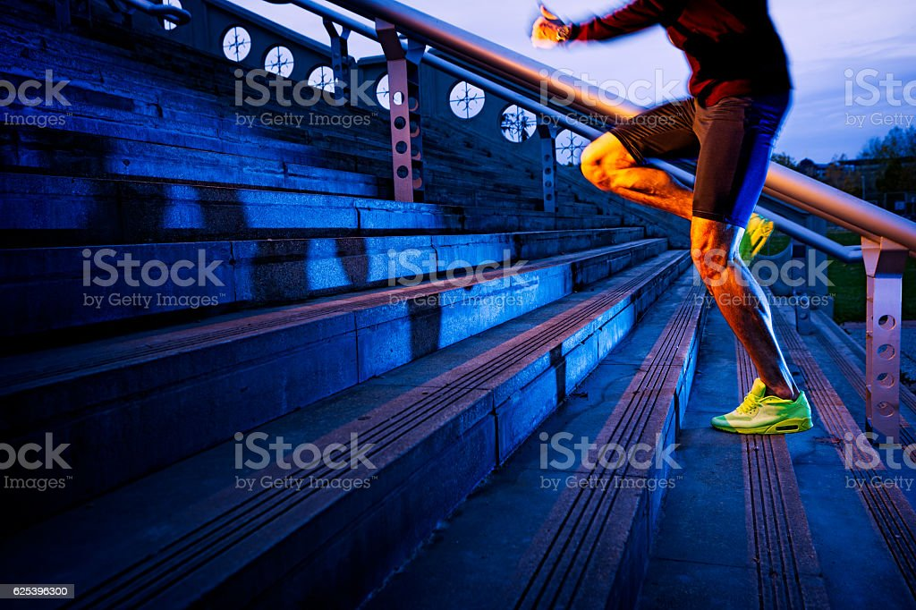 Practice, close up of young man running up the stairs stock photo
