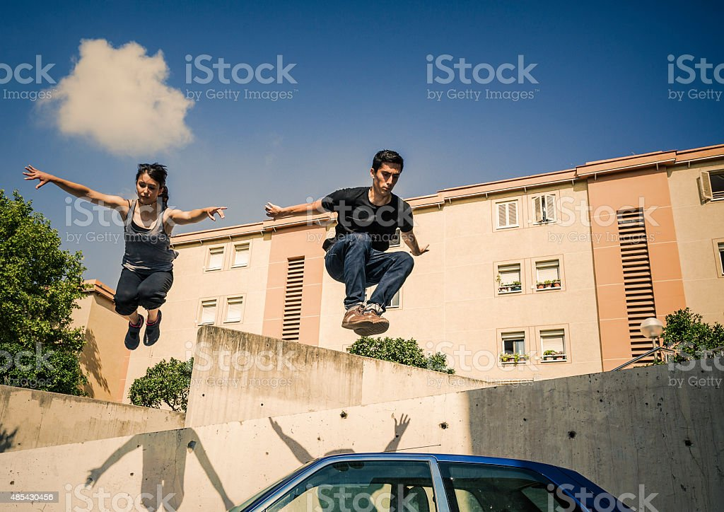 Urban parkour Young man and woman jumping over car