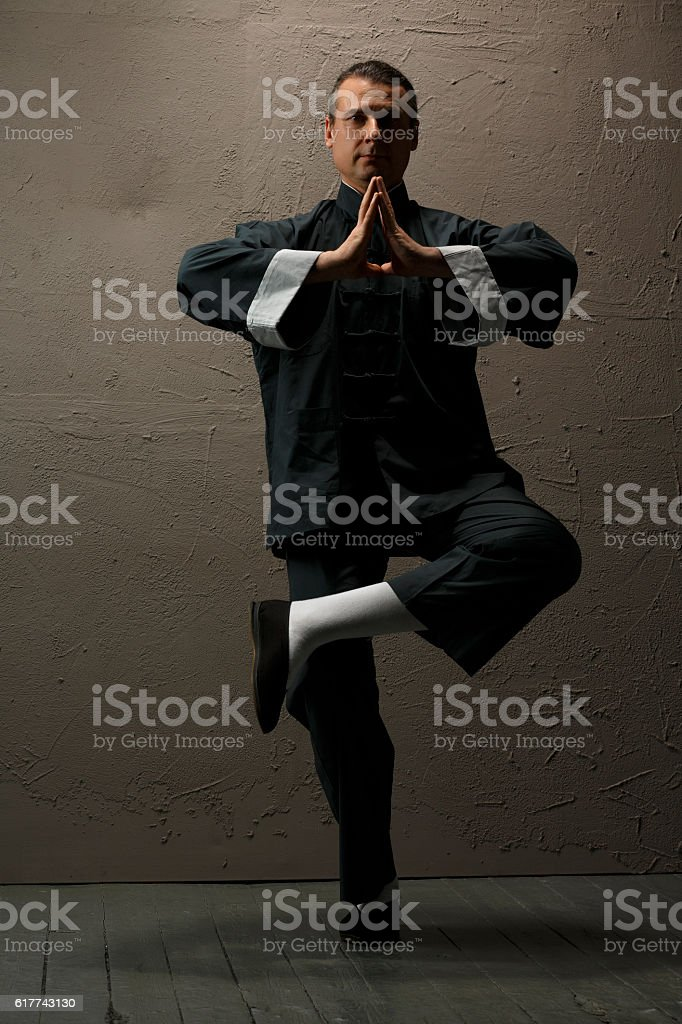 Practicing Tai Chi    Man in kimono excercising martial arts stock photo