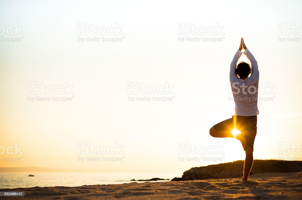 Practicing yoga and meditation in summer on beach in sunset stock photo
