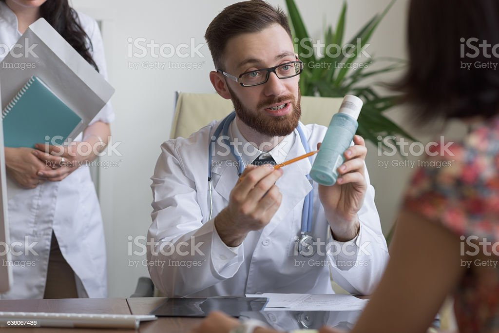 Practitioner consulting woman about body lotion stock photo