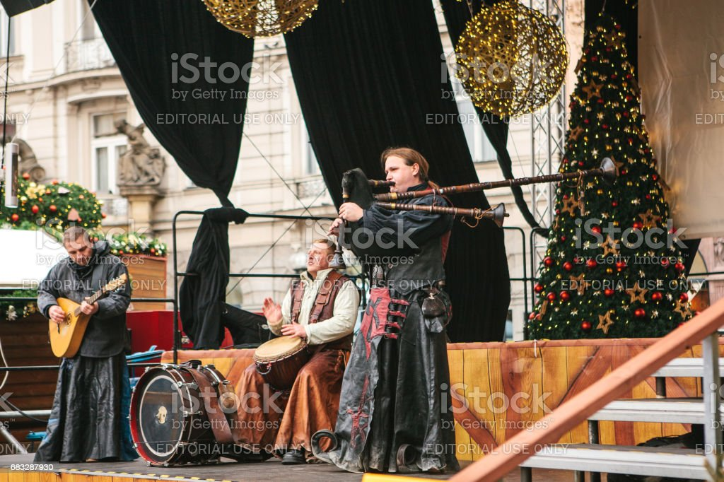 Prague, Czech Republic, December 13, 2016: Christmas performance on stage in Prague's main square. The ethnic collective plays on bagpipes and other national instruments. Christmas in Europe. stock photo