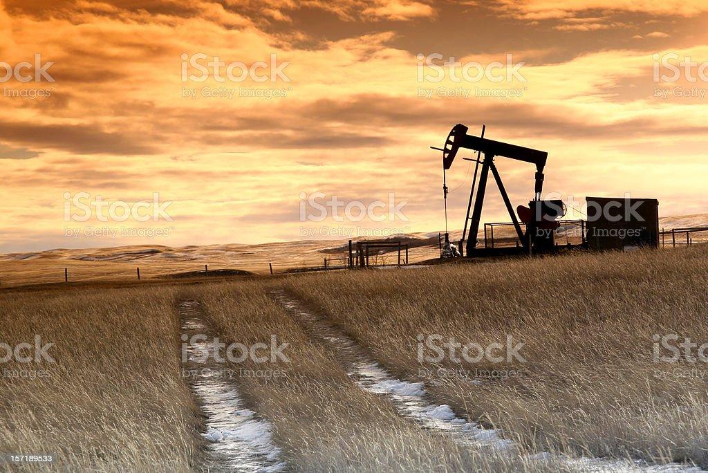 Prairie Pumpjack with Dramatic Sunset Sky stock photo