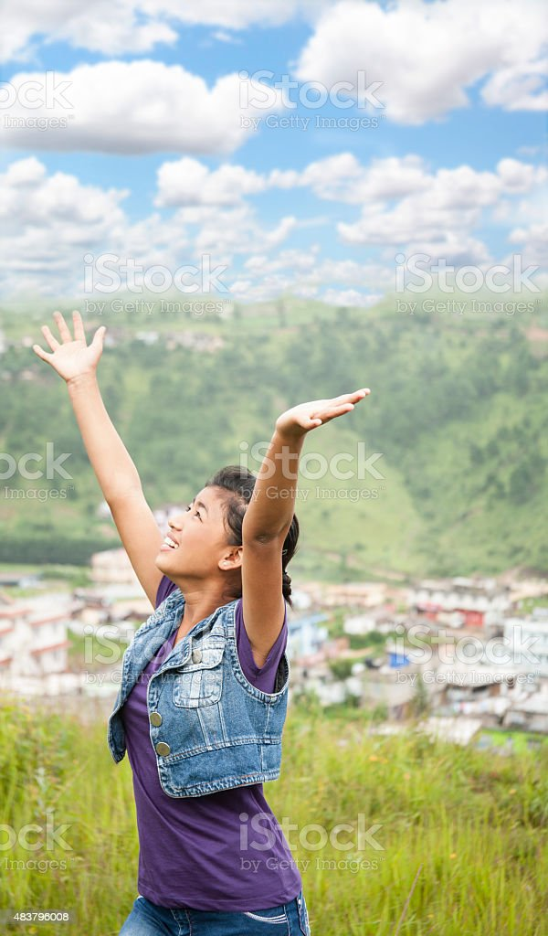 Praise! Asian girl gives thanks as she lifts arms upward. stock photo