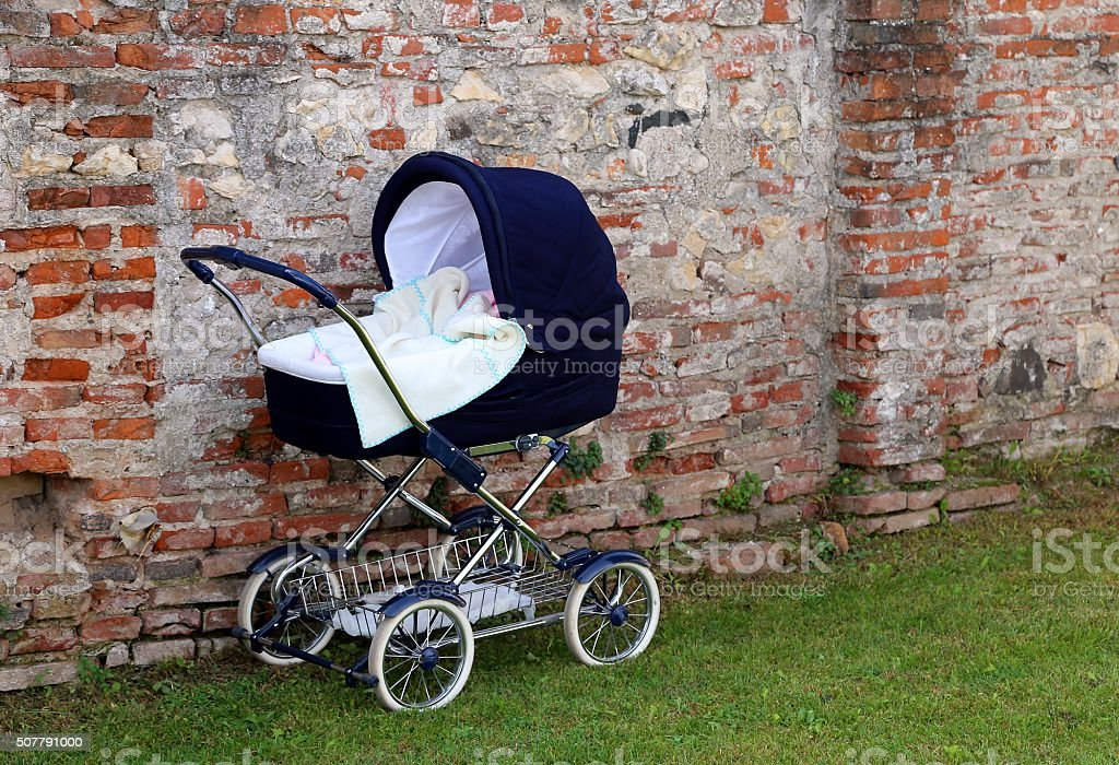 pram for newborn babies on the garden and the wall stock photo