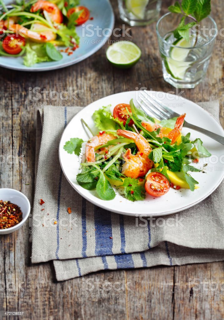 Prawn salad on a white plate on a wooden table stock photo