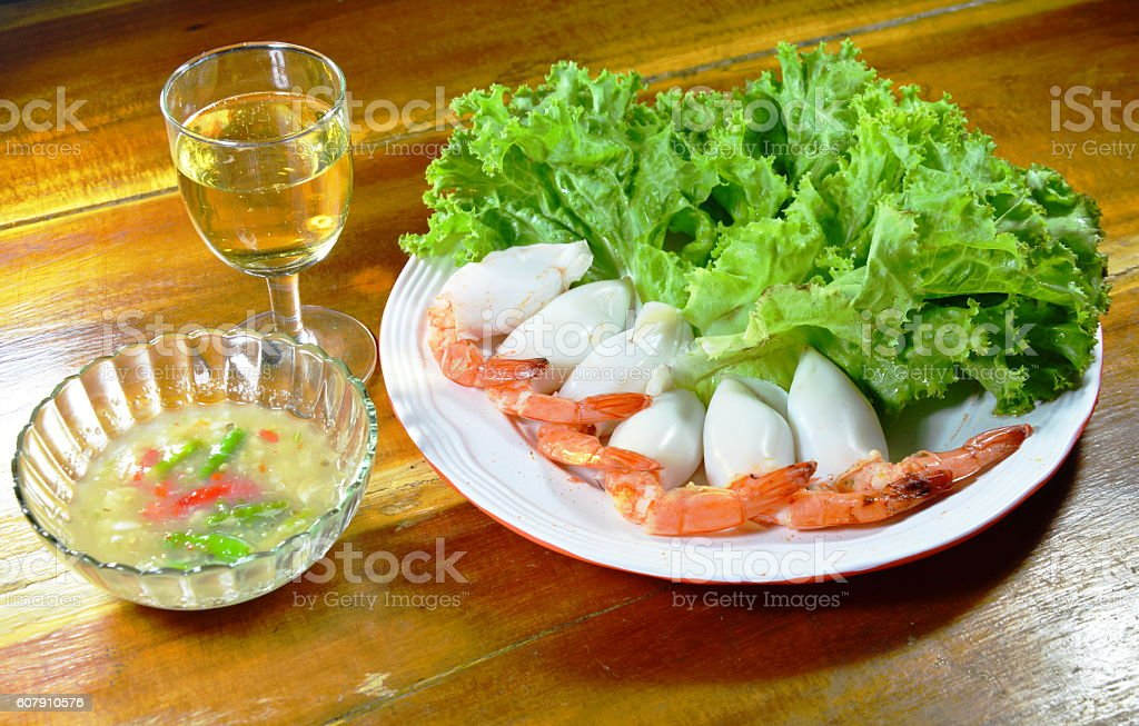prawn stuffed squid cocktail with spicy sauce and sparking drink stock photo