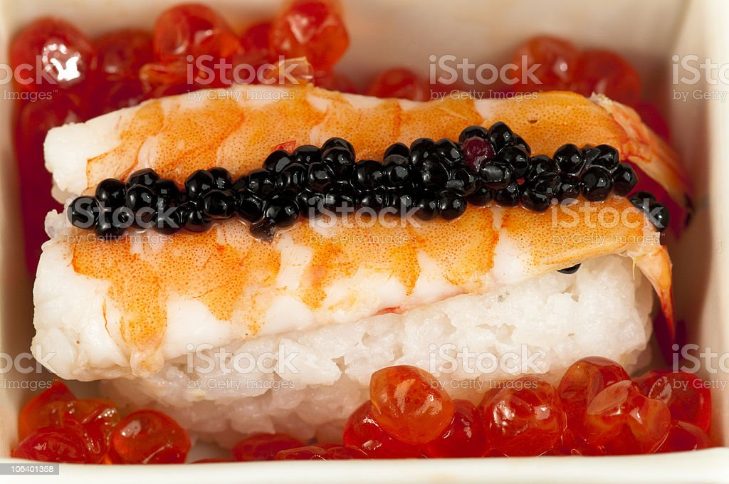 Prawn  sushi garnished with  black fish roe on salmon eggs. royalty-free stock photo