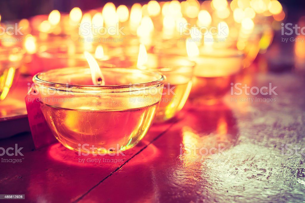 Pray candle glass on wood table in chinese temple stock photo