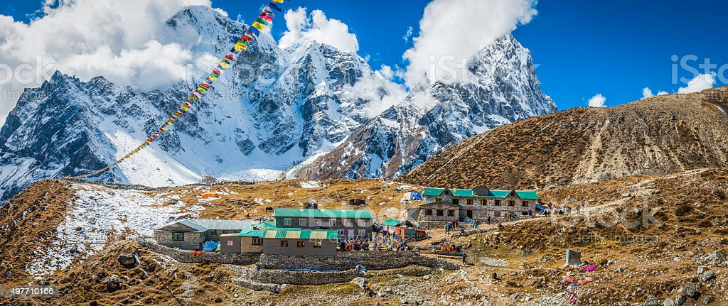 Prayer flags flying over Sherpa teahouse Khumbu mountains Himalayas Nepal stock photo