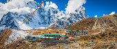 Prayer flags flying over Sherpa teahouse Khumbu mountains Himalayas Nepal