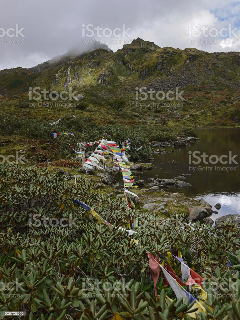Prayer flags in high Himalayas along isolated bank of lake. stock photo