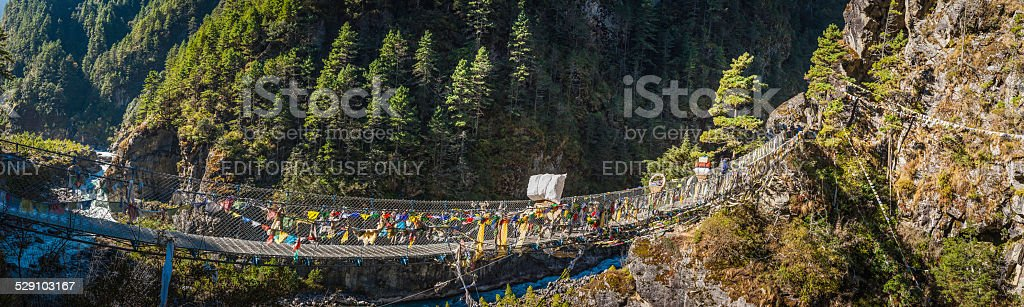 Prayer flags on rope bridge over canyon Himalaya mountains Nepal stock photo