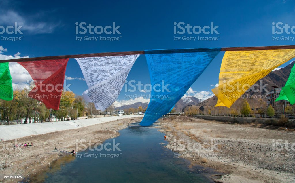 Prayer flags over a river in Lhasa stock photo