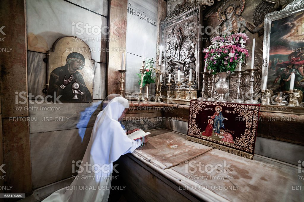 Prayer in the tomb of Jesus Christ stock photo